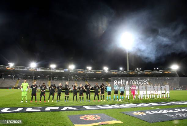 In this handout image provided by UEFA, The Manchester United and LASK teams line up in a empty stadium prior to the UEFA Europa League round of 16...