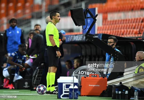 In this handout image provided by UEFA The Match Referee checks the VAR screen for a penalty decision which is later awarded to Atalanta during the...