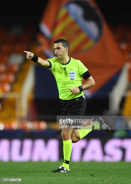 In this handout image provided by UEFA The match referee points to the penalty spot after a VAR review awards a penalty to Atalanta during the UEFA...