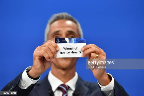 In this handout image provided by UEFA UEFA Champions League Ambassador Paulo Sousa draws out the card of 'Winner of quarterfinal 3' during the UEFA...
