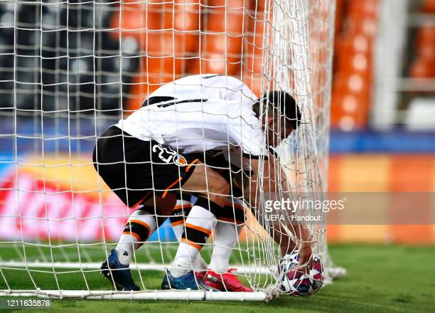 In this handout image provided by UEFA Valencia players collect the ball from the net during the UEFA Champions League round of 16 second leg match...