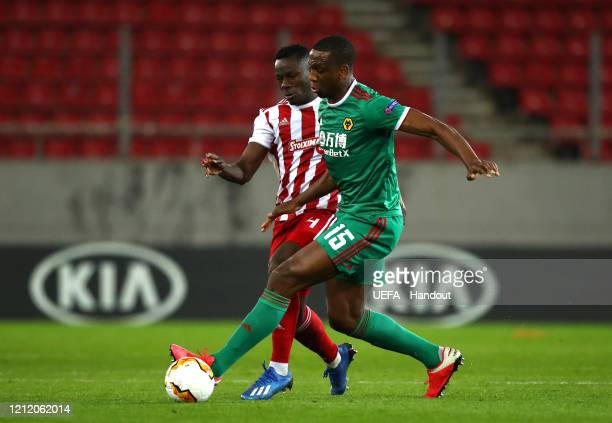 In this handout image provided by UEFA Willy Boly of Wolverhampton Wanderers is challenged by Mady Camara of Olympiacos FC during the UEFA Europa...