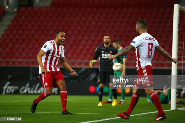 In this handout image provided by UEFA Youssef El Arabi of Olympiacos FC celebrates with Guilherme after scoring his team's first goal during the...