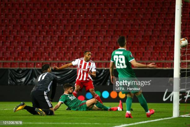 In this handout image provided by UEFA, Youssef El Arabi of Olympiacos FC scores his team's first goal during the UEFA Europa League round of 16...