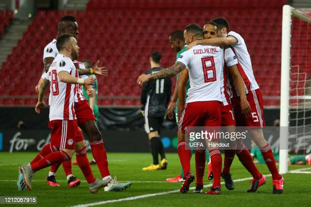 In this handout image provided by UEFA Youssef El Arabi of Olympiacos FC celebrates with his team mates after scoring his team's first goal during...