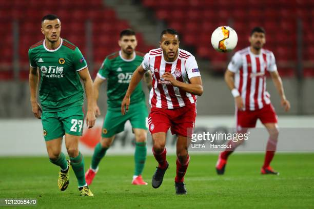 In this handout image provided by UEFA Youssef El Arabi of Olympiacos FC runs after the ball with Romain Saiss of Wolverhampton Wanderers during the...