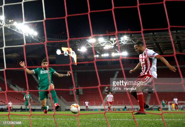 In this handout image provided by UEFA Youssef El Arabi of Olympiacos FC scores his team's first goal during the UEFA Europa League round of 16 first...