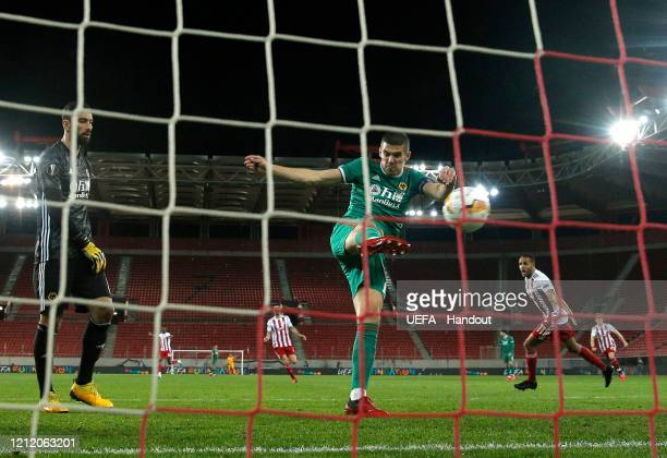 In this handout image provided by UEFA Youssef El Arabi of Olympiacos FC celebrates after scoring his team's first goal as Conor Coady and Rui...
