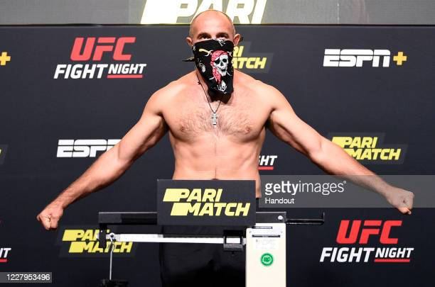 In this handout image provided by UFC, Aleksei Oleinik of Russia poses on the scale during the UFC Fight Night weigh-in at UFC APEX on August 07,...