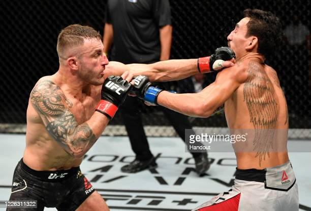 In this handout image provided by UFC Alexander Volkanovski of Australia punches Max Holloway in their UFC featherweight championship fight during...