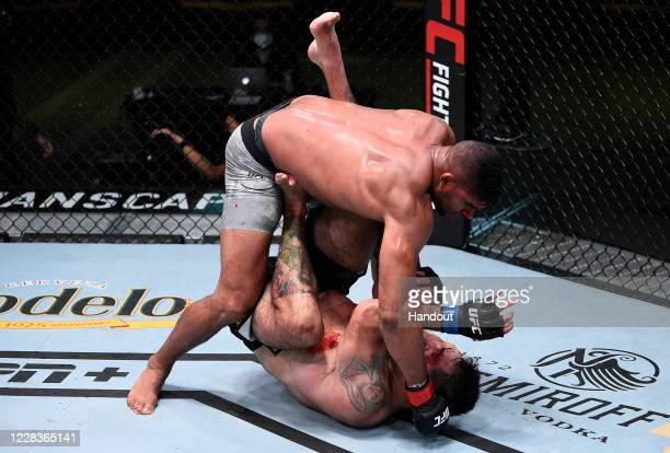 In this handout image provided by UFC, Alistair Overeem of the Netherlands punches Augusto Sakai of Brazil in a heavyweight fight during the UFC...
