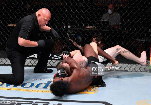 In this handout image provided by UFC Aljamain Sterling attempts to secure a rear choke submission against Cory Sandhagen in their bantamweight bout...