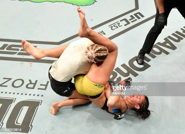 In this handout image provided by UFC, Amanda Ribas of Brazil secures an arm bar submission against Paige VanZant in their flyweight fight during the...