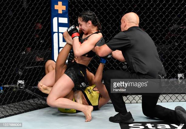 In this handout image provided by UFC, Ariane Lipski of Brazil secures a knee bar submission against Luana Carolina of Brazil in their flyweight bout...