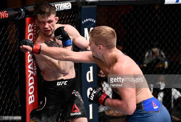 In this handout image provided by UFC, Austin Hubbard punches Max Rohskopf in their lightweight bout during the UFC Fight Night event at UFC APEX on...