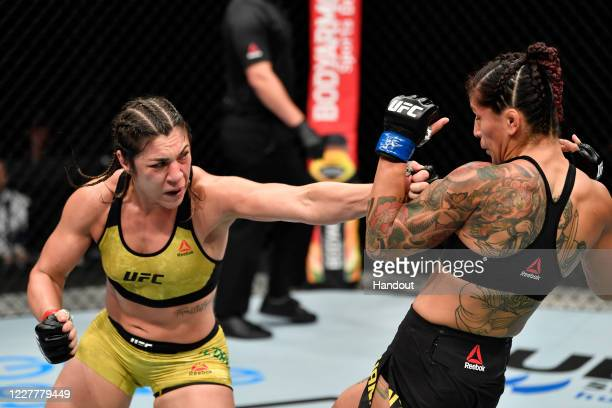In this handout image provided by UFC Bethe Correia of Brazil punches Pannie Kianzad of Iran in their bantamweight fight during the UFC Fight Night...