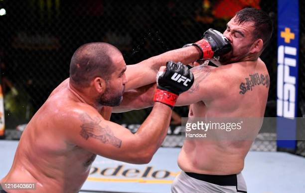 In this handout image provided by UFC Blagoy Ivanov of Bulgaria punches Augusto Sakai of Brazil in their heavyweight fight during the UFC Fight Night...