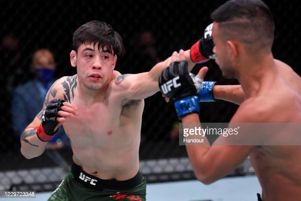 In this handout image provided by UFC, Brandon Moreno of Mexico punches Brandon Royval in their flyweight bout during the UFC 255 event at UFC APEX...