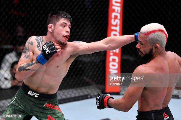 In this handout image provided by UFC, Brandon Moreno of Mexico punches Deiveson Figueiredo of Brazil in their flyweight championship bout during the...