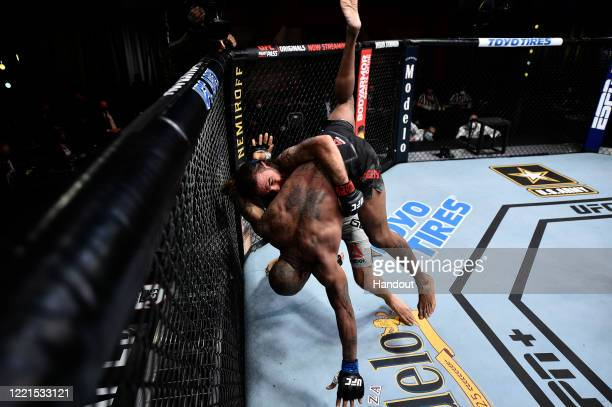In this handout image provided by UFC Clay Guida takes down Bobby Green in their lightweight bout during the UFC Fight Night event at UFC APEX on...
