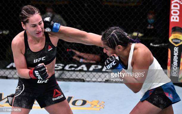 In this handout image provided by UFC, Cynthia Calvillo punches Jessica Eye in their flyweight fight during the UFC Fight Night event at UFC APEX on...