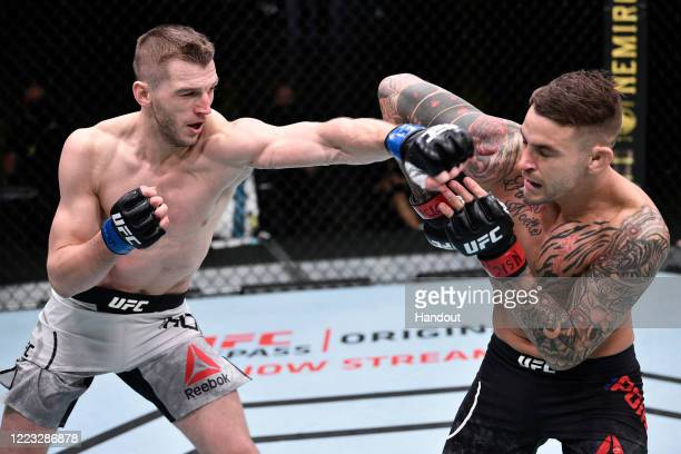 In this handout image provided by UFC, Dan Hooker of New Zealand punches Dustin Poirier in their lightweight fight during the UFC Fight Night event...