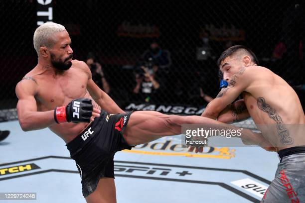 In this handout image provided by UFC, Deiveson Figueiredo of Brazil kicks Alex Perez in their flyweight championship bout during the UFC 255 event...
