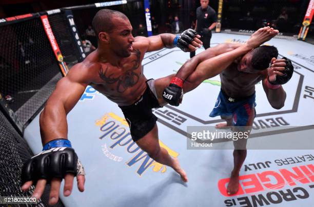 In this handout image provided by UFC Devin Clark kicks Alonzo Menifield in their light heavyweight bout during the UFC 250 event at UFC APEX on June...