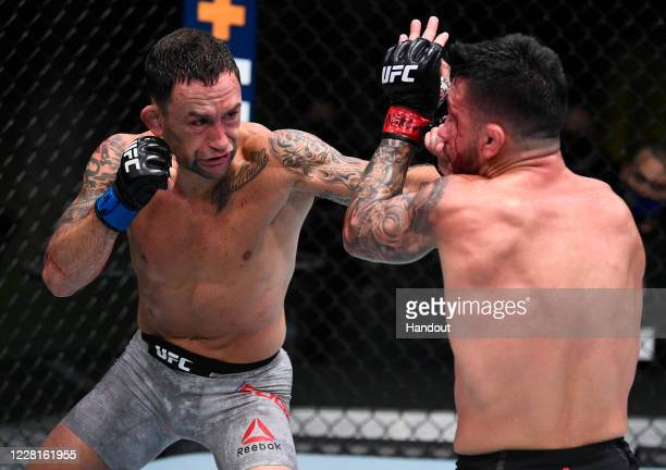In this handout image provided by UFC, Frankie Edgar punches Pedro Munhoz of Brazil in their bantamweight fight during the UFC Fight Night event at...