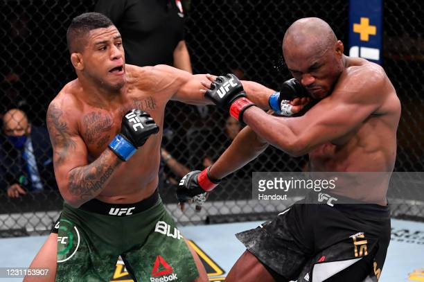 In this handout image provided by UFC, Gilbert Burns of Brazil punches Kamaru Usman of Nigeria in their UFC welterweight championship fight during...