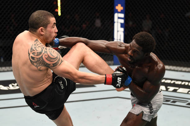 In this handout image provided by UFC, Jared Cannonier punches Robert Whittaker of Australia in their middleweight bout during the UFC 254 event on...