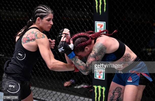 In this handout image provided by UFC, Julia Avila punches Gina Mazany in their bantamweight fight during the UFC Fight Night event at UFC APEX on...