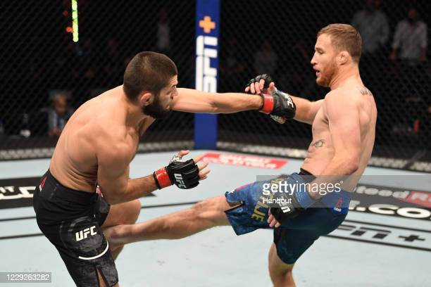 In this handout image provided by UFC, Justin Gaethje kicks Khabib Nurmagomedov of Russia in their lightweight title bout during the UFC 254 event on...