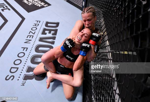 In this handout image provided by UFC Katlyn Chookagian attempts to secure a rear choke submission against Antonina Shevchenko of Kyrgyzstan in their...