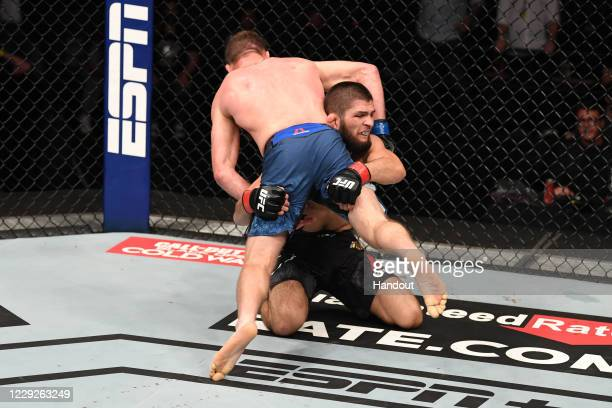 In this handout image provided by UFC, Khabib Nurmagomedov of Russia takes down Justin Gaethje in their lightweight title bout during the UFC 254...