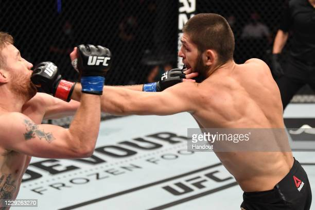 In this handout image provided by UFC, Khabib Nurmagomedov of Russia punches Justin Gaethje in their lightweight title bout during the UFC 254 event...