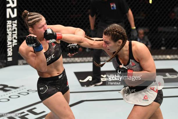 In this handout image provided by UFC, Liana Jojua of Georgia punches Miranda Maverick in their women's flyweight bout during the UFC 254 event...