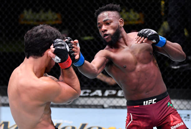 In this handout image provided by UFC, Manel Kape of Angola punches Alexandre Pantoja of Brazil in their flyweight fight during the UFC Fight Night...