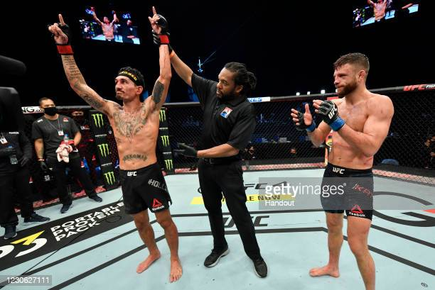 In this handout image provided by UFC, Max Holloway celebrates after his unanimous-decision victory over Calvin Kattar in a featherweight bout during...