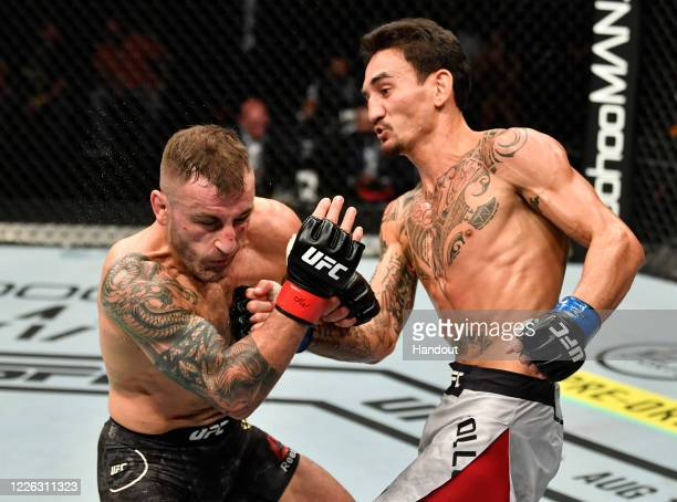 In this handout image provided by UFC Max Holloway punches Alexander Volkanovski of Australia in their UFC featherweight championship fight during...