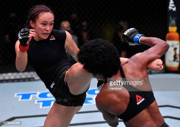 In this handout image provided by UFC, Michelle Waterson kicks Angela Hill in a strawweight fight during the UFC Fight Night event at UFC APEX on...