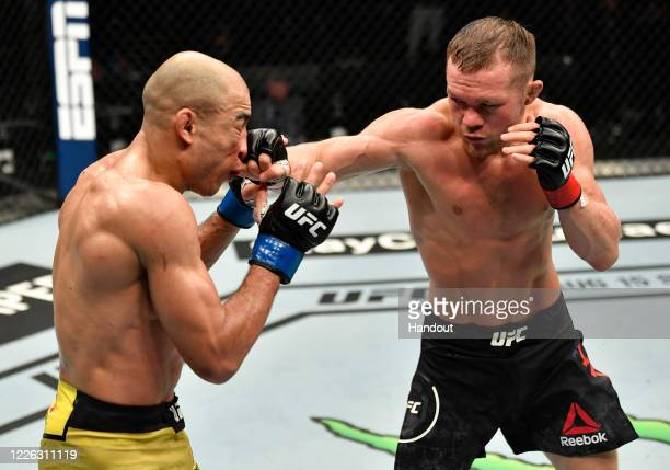 In this handout image provided by UFC, Petr Yan of Russia punches Jose Aldo of Brazil in their UFC bantamweight championship fight during the UFC 251...