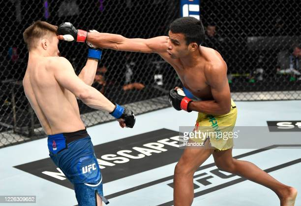 In this handout image provided by UFC, Raulian Paiva of Brazil punches Zhalgas Zhumagulov of Kazakhstan in their flyweight fight during the UFC 251...