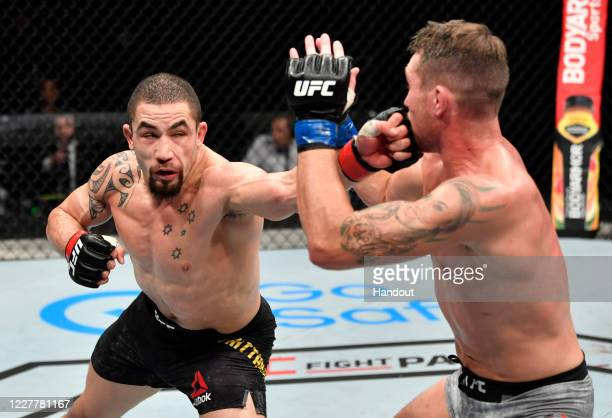 In this handout image provided by UFC Robert Whittaker of New Zealand punches Darren Till of England in their middleweight fight during the UFC Fight...