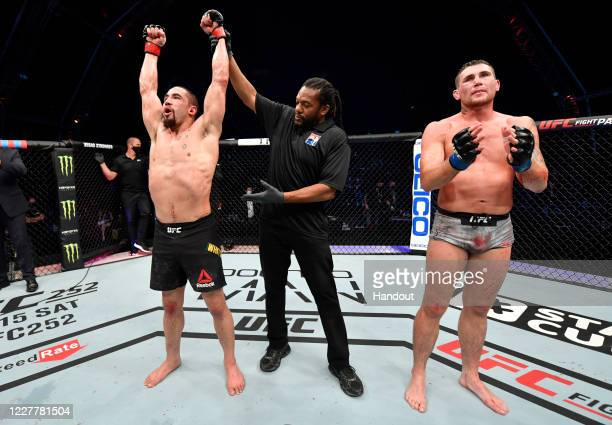 In this handout image provided by UFC Robert Whittaker of New Zealand celebrates after his victory over Darren Till of England in their middleweight...