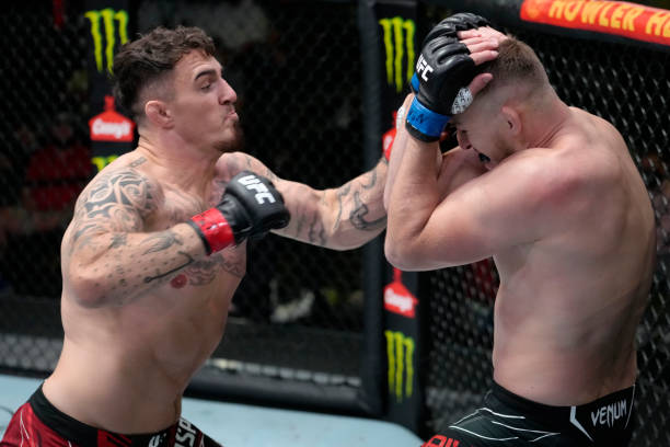 In this handout image provided by UFC, Tom Aspinall of England punches Serghei Spivak of the Ukraine in their welterweight fight during the UFC Fight...