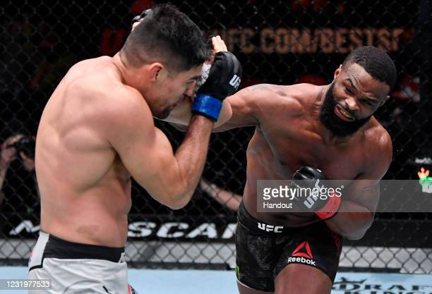 In this handout image provided by UFC, Tyron Woodley punches Vicente Luque in their welterweight fight during the UFC 260 event at UFC APEX on March...