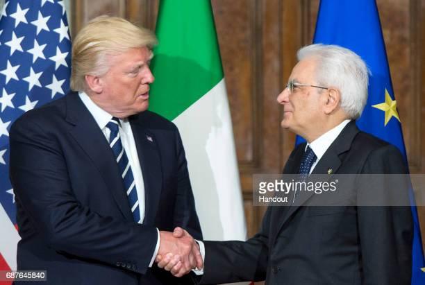 In this handout image provided by Ufficio Stampa e Comunicazione della Presidenza della Repubblica US President Donald Trump shake hands with Italian...