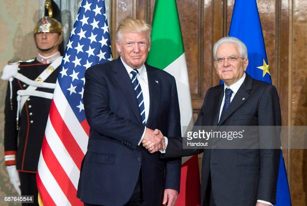 In this handout image provided by Ufficio Stampa e Comunicazione della Presidenza della Repubblica, US President Donald Trump shake hands with...