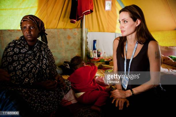 In this handout image provided by UNHCR UNHCR Goodwill Ambassador Angelina Jolie visits Somali refugees at Shousha Camp located eight kilometres from...